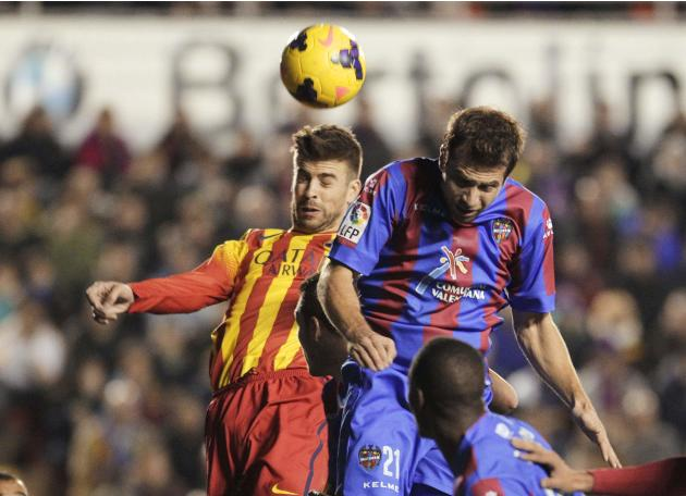 Barcelona's Pique heads the ball to score next to Levante's Ivanschitz during their Spanish First Division soccer match at the Ciudad de Valencia stadium in Valencia