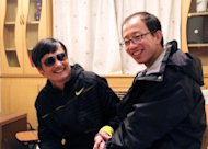 An undated photo shows outspoken government critic Hu Jia (R) sharing a light moment with blind lawyer Chen Guangcheng after his escape, at an undisclosed location in Beijing. Hu, who was detained over the weekend for questioning in the affair, also said Chinese security officials indicated that Chen had met with US ambassador Gary Locke since the activist&#39;s dramatic flight from house arrest