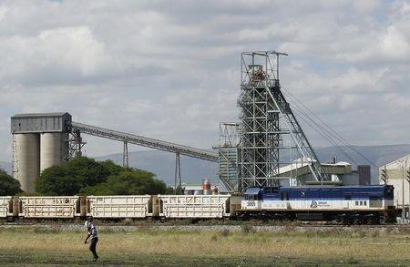 A man walks past a train carrying goods, at Anglo Platinum's Khomanani shaft 1 mine in Rustenburg