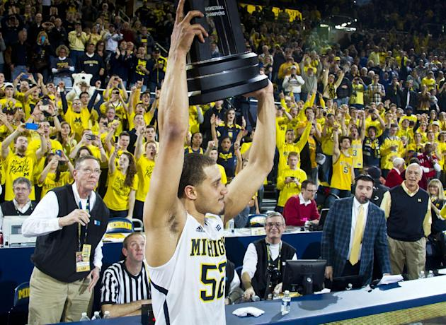Michigan forward Jordan Morgan holds up the Big Ten Basketball Champions trophy after an NCAA college basketball game against Indiana in Ann Arbor, Mich., Saturday, March 8, 2014. Michigan won 84-80.