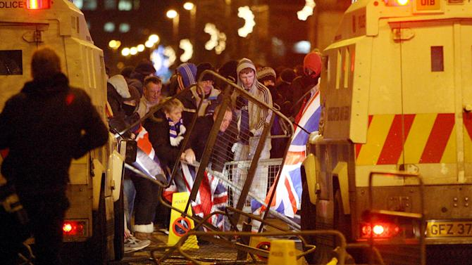 Loyalist protestors, some of them carrying British flags, clash with police as city councilors debate whether or not to keep the flag flying at City Hall, outside City Hall, Belfast, Northern Ireland, Monday, Dec. 3, 2012. A Protestant mob stormed into the grounds of Belfast City Hall and clashed with police after the council's Catholic majority voted to remove the British flag from the building for most of the year. Authorities say two police officers and a security guard were wounded during Monday night's melee in the parking lot of the city hall. (AP Photo/PA, Paul Faith) UNITED KINGDOM OUT, NO SALES, NO ARCHIVE