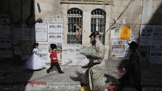 Ultra-Orthodox Jewish children dressed in costumes walk outside during celebrations marking Purim in Jerusalem