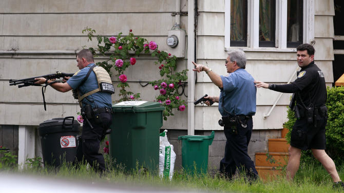 Police surround a house in the University district in Seattle near a cafe where a gunman killed two people and critically wounded three others Wednesday, May 30, 2012. The shooting took place about 11 a.m. at Cafe Racer, a restaurant and music venue north of the University of Washington. (AP Photo/Elaine Thompson)