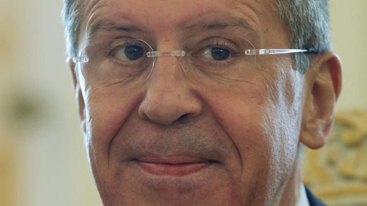 Russian Foreign Minister Sergey Lavrov smiles while welcoming his Mozambique counterpart Oldemiro Marques Baloi during their meeting in Moscow, Russia, on Monday, April 21, 2014. (AP Photo/Ivan Sekretarev)