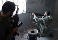A rebel fighter fires his weapon towards pro-Syrian government troops in the Bustan al-Bashar district of the northern Syrian city of Aleppo