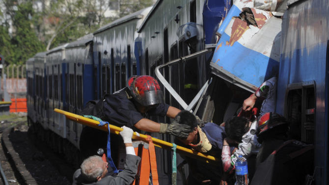 FILE - In this Feb. 22, 2012 file photo, firemen rescue wounded passengers from a commuter train after a collision in Buenos Aires, Argentina.  Argentina's government is revoking the concession of the company whose commuter train ran crashed in Buenos Aires in February, killing as many as 51 people and injuring hundreds. Planning Minister Julio de Vido says the Trains of Buenos Aires company failed to adequately maintain the trains, and that their capacity and quality of services were in serious decline before the crash in February. (AP Photo/Leonardo Zavattaro,Telam, File)