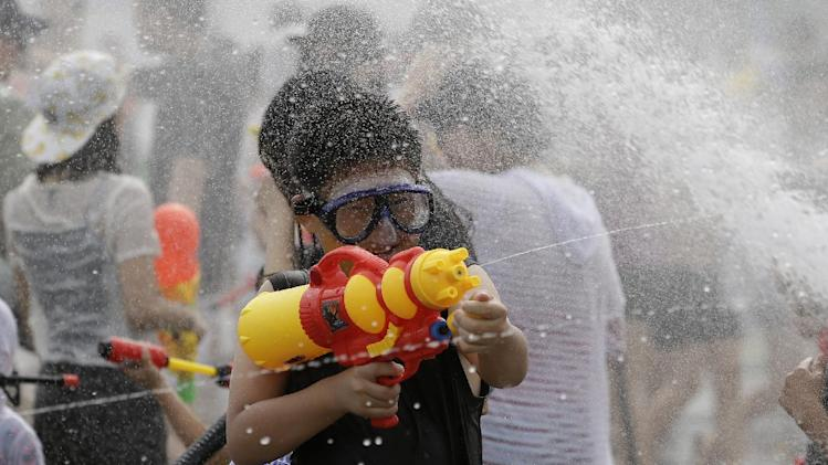 A boy sprays his water gun during the Han River Splash Game festival in Seoul, South Korea, Friday, Aug. 1, 2014. South Korean Meteorological Administration issued a heat wave warning for Seoul for the first time in 2014. (AP Photo/Lee Jin-man)