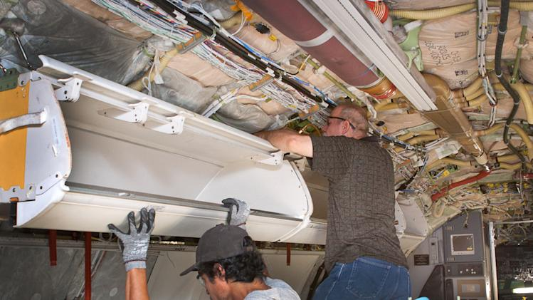 This undated photo provided by American Airlines parent company AMR, shows workers installing larger bins for carry-on luggage on a Boeing 737, in Tulsa, Okla. Fliers can stop sharpening their elbows. Overhead bins are getting bigger. (AP Photo/AMR)