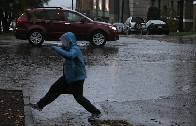 A pedestrian navigates around standing water, Monday, Nov. 19, 2012, at an intersection in Tacoma, Wash. Wet and windy weather with mountain snow will continue this week in Washington, forecasters sai