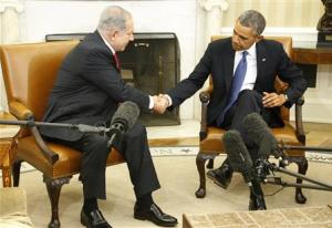 Netanyahu shakes hands with Obama as they sit down to meet in the Oval Office of the White House in Washington