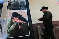 "A US Border Patrol agent passes photos of slain agent Brian Terry during a memorial service on January 21, 2011 in Tucson, Arizona. The botched ""Fast and Furious"" operation, a US effort to track guns into Mexico that left drug cartels with high-powered weapons, was launched in 2009, but was suspended after the border agent's killing"