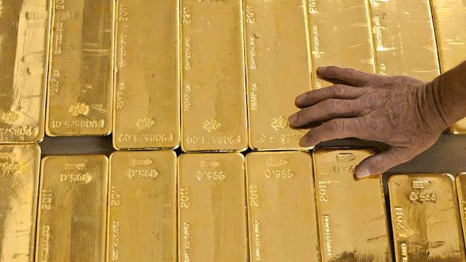 FILE - In this Aug. 8, 2011 file photo a person touches gold bars in the gold store of the Cantonal Bank of Zurich ZKB in Zurich, Switzerland.  In Switzerland, a campaign is on to protect the country's wealth by investing in gold _ a lot of gold. In a test of their sense of financial security, the Swiss are being asked to vote on a proposal to make the central bank hold a fifth of its reserves in gold within five years. That would mean buying 1,500 metric tons, or 1,650 short tons, of gold worth more than US$60 billion. (AP Photo/Keystone, Martin Ruetschi) EDITORIAL USE ONLY, NO SALES, NO ARCHIVES