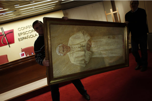 Workers remove a painting of Pope Benedict XVI from the press conference room after the head of Spain's Catholic Church and President of the Bishops' Conference Cardinal Antonio Maria Rouco Varela add