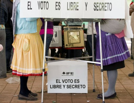 "<p>Two Mazahua indigenous women vote next to a sign reading ""The vote is free and secret"" during presidential elections in San Pedro el Alto, Mexico State, on July 1, 2012. Enrique Pena Nieto, the youthful candidate of the party that governed Mexico for decades, won a resounding victory in the country's presidential election, exit polls showed.</p>"