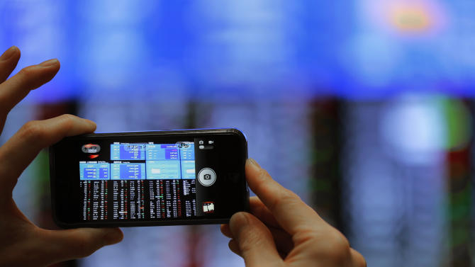 A visitor takes a picture of an electronic stock board on the Tokyo Stock Exchange in Tokyo, Wednesday, May 22, 2013. Asian stock markets were mostly higher Wednesday after investor confidence was boosted by a Federal Reserve official's comments that the U.S. central bank should stick with its super-easy monetary policy. (AP Photo/Itsuo Inouye)