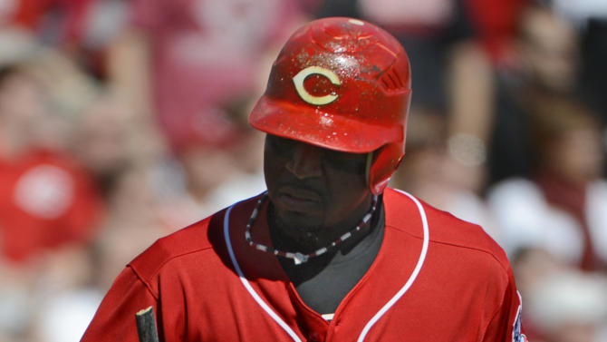 Cincinnati Reds' Brandon Phillips looks at what remains of his bat as he runs up the first base line after breaking the bat lining out to center field in the first inning of Game 5 of the National League division baseball series against the San Francisco Giants, Thursday, Oct. 11, 2012, in Cincinnati. (AP Photo/Michael Keating)