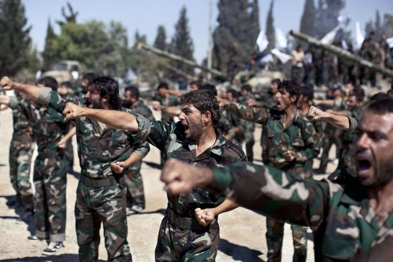 Members of rebel brigades parade on September 13, 2013 at a former military academy north of Aleppo