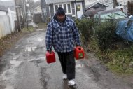 Joe Graham delivers some gas in the snow to a neighbor for use in her generator in the New Dorp section of Staten Island, N.Y. Wednesday, Nov. 7, 2012. A nor&#39;easter blustered into New York and New Jersey on Wednesday, threatening to swamp homes all over again, plunge neighborhoods back into darkness and inflict more misery on tens of thousands of people still reeling from Superstorm Sandy. (AP Photo/Seth Wenig)