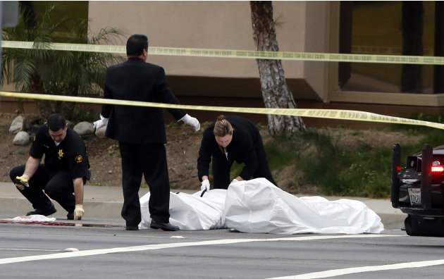 Orange County coroner's officials remove a body from the scene in Orange, Calif., Tuesday, Feb. 19, 2013. Police say a chaotic 25-minute shooting spree through Orange County left a trail of dead and i