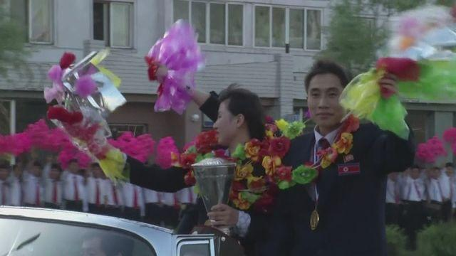 Triumphant North Koreans return home