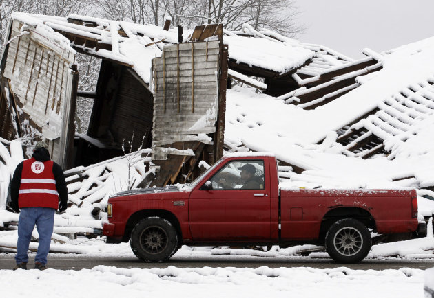 A resident drives around a house left damaged by Friday&#39;s tornado in Marysville, Ind., Monday, March 5, 2012. (AP Photo/Nam Y. Huh)