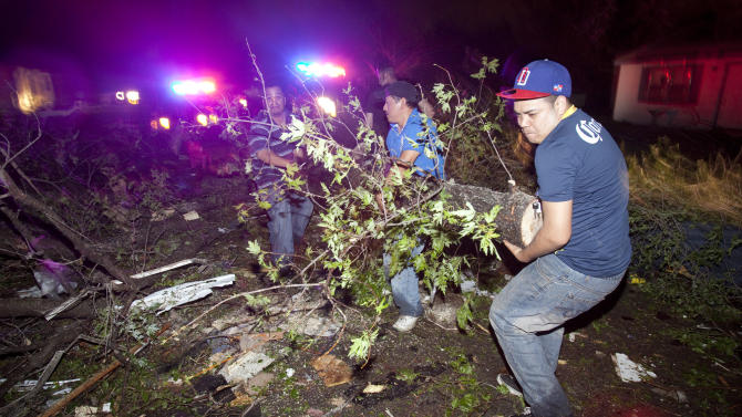 """Residents of a south Wichita neighborhood clean up fallen trees after a tornado caused massive destruction in the Wichita, Kan.-area on Saturday night, April 14, 2012. Tornadoes were spotted across the Midwest and Plains on Saturday as an outbreak of unusually strong weather seized the region, and forecasters sternly warned that """"life-threatening"""" weather could intensify overnight. (AP Photo/The Wichita Eagle, Travis Heying) MAGS OUT; TV OUT"""