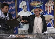 Zabulon Simantov (R), an Afghan Jew, fans kebabs being grilled for customers, at his cafe in Kabul November 5, 2013. REUTERS/Omar Sobhani