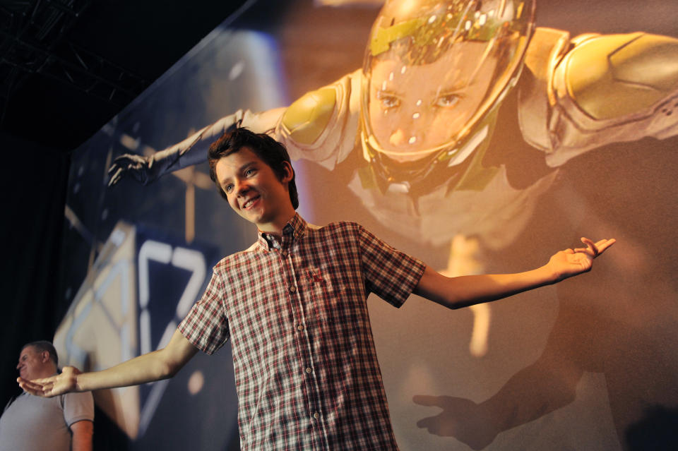 "Asa Butterfield, a cast member in the forthcoming film ""Ender's Game,"" poses underneath a picture of his character in the film at a preview event for the film at the 2013 Comic-Con International Convention on Wednesday, July 17, 2013 in San Diego, Calif. (Photo by Chris Pizzello/Invision/AP)"