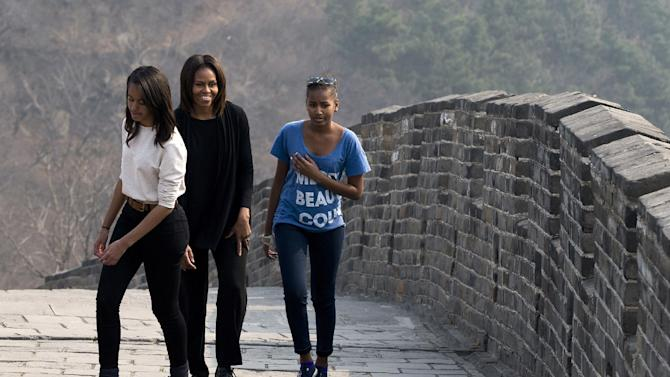FILE - This March 23, 2014 file photo shows first lady Michelle Obama walking with her daughters Malia, left, and Sasha, right, as they visit the Mutianyu section of the Great Wall of China in Beijing. When President Barack Obama travels abroad, getting just the leader of the free world doesn't seem to be enough. Countries want the first lady, too. But Michelle Obama won't join her husband when he heads to Asia next week and her absence is likely to sting, especially in Japan. It's the first of four countries on Obama's travel schedule and the only one welcoming him on an official state visit. (AP Photo/Andy Wong, File)