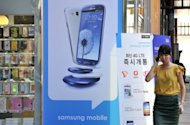 A woman walks past a signboard for the Samsung Galaxy S3 at a mobile phone shop in Seoul. South Korea&#39;s Samsung Electronics vowed on Tuesday to take &quot;all necessary measures&quot; to keep its products on US store shelves, in response to Apple&#39;s request for a ban on sales of some smartphones