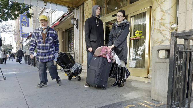 A man, left, leaves the Cecil Hotel with belongings as Michael and Sabina Baugh, both 27, of Plymouth, England, wait for transportation as they leave the hotel in downtown Los Angeles Wednesday, Feb. 20, 2013.  Early Tuesday, police discovered the body of a Canadian woman at the bottom of the historic hotel's water tank, weeks after she was reported missing.  The Baughs, on a 14-day tour package, had been there eight days and had showered in and drank the water. The couple's tour operator was less than cooperative in finding them other accommodations.  (AP Photo/Reed Saxon)