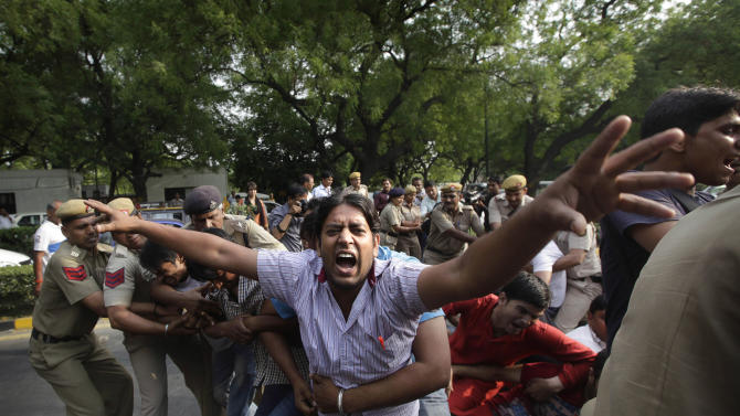 Indian policemen try to remove protestors shouting slogans outside Prime Minister's residence during a protest against the rape of a 5-year-old girl in New Delhi, India, Sunday, April 21, 2013. The girl was allegedly kidnapped, raped and tortured by a man and then left alone in a locked room in India's capital for two days. (AP Photo/Manish Swarup)