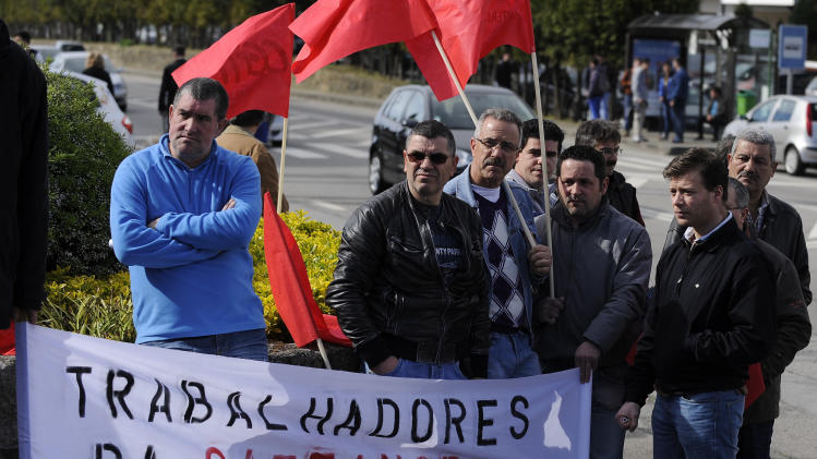 Workers from the bus factory of  Portuguese automakers group Salvador Caetano, protest at the factory gates against the temporary suspension of work  covering 98 workers for a period of six months Tuesday, April 2, 2013, in Vila Nova de Gaia, Portugal. Official figures Tuesday showed that unemployment across the 17 European Union countries that use the euro has struck 12 percent for the first time since the currency was launched in 1999.(AP Photo/Paulo Duarte)