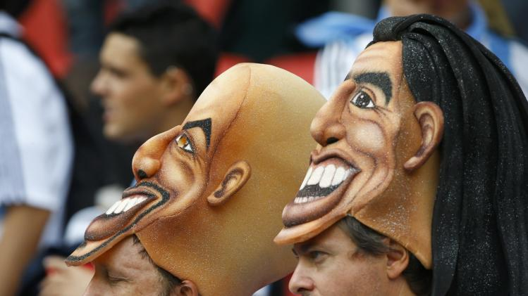 Argentina fans wear masks of former Argentine soccer players Maradona and Veron during their 2014 World Cup Group F soccer match against Nigeria at the Beira Rio stadium in Porto Alegre