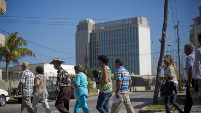In this photo taken Jan. 13, 2014, people walk in line while entering the U.S. Interests Section to apply for U.S. travel visas in Havana, Cuba. Cubans are taking advantage of a travel reform that went into effect a year ago, when the government scrapped an exit visa requirement that for five decades had made it difficult for most islanders to go abroad. Now they are traveling in record numbers. (AP Photo/Ramon Espinosa)