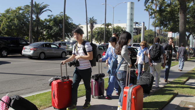 Passengers walk with their luggage on a city street outside Los Angeles International Airport on Friday Nov. 1, 2013 after shots were fired in Terminal 3, prompting authorities to evacuate terminals and stop flights headed for the city from taking off from other airports. (AP Photo/Nick Ut)