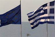 <p>A Greek (R) and an EU flag fly over the Greece's Finance Ministry in Athens November 3, 2011. REUTERS/Yannis Behrakis</p>