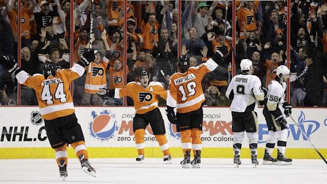 Philadelphia Flyers' Kimmo Timonen, from left, of Finland, Danny Briere and Scott Hartnell celebrate after Hartnell's game-winning goal in overtime as Pittsburgh Penguins' Pascal Dupuis and Kris Letang skate off the ice after an NHL hockey game Sunday, March 18, 2012, in Philadelphia. Philadelphia won 3-2 in overtime. (AP Photo/Matt Slocum)