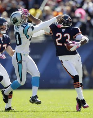 Chicago Beas' Devin Hester (23) gives a stiff-arm to Carolina Panthers' Olindo Mare (10) on the way to a 69-yard punt return for a touchdown in the first half of an NFL football game in Chicago, Sunday, Oct. 2, 2011. (AP Photo/Nam Y. Huh)