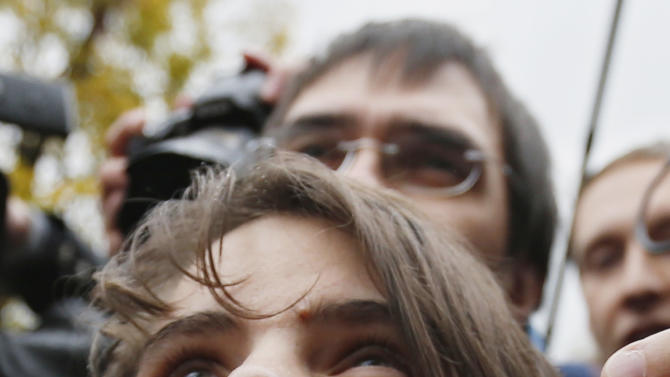 Freed feminist punk group Pussy Riot member Yekaterina Samutsevich speaks outside a court in Moscow, Wednesday Oct. 10, 2012. A Moscow appeals court on Wednesday unexpectedly freed one of the jailed Pussy Riot members, but upheld the two-year prison sentence for the two others jailed for an irreverent protest against President Vladimir Putin.  The Moscow City Court ruled that Yekaterina Samutsevich's sentence should be suspended because she was thrown out of the cathedral by guards before she could remove her guitar from its case and take part in the performance.  (AP Photo/Sergey Ponomarev)