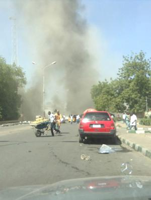In this photo taken with a mobile phone, people runs as smokes billows through the sky after a car bomb explosion at a military post in Maiduguri, Nigeria, Tuesday, Jan. 14, 2014. A vehicle exploded at a military post in a commercial area in a northeastern Nigerian city on Tuesday, killing at least 17 people and causing pandemonium with blood-spattered bystanders running away and vehicles colliding as drivers rushed to flee. (AP Photo/Abdulkareem Haruna)