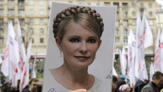 FILE - In this Wednesday, Oct. 23, 2013 file photo, an activist of the Ukrainian Opposition Party holds a poster with a photo of former Ukrainian Prime Minister Yulia Tymoshenko outside the Kiev City council building, during a protest rally demanding a re-election of the city council, in Kiev, Ukraine. More than 20 years after gaining independence from the Soviet Union and painfully searching for its place on the geopolitical map, Ukraine finally has a real chance to firmly align itself with the EU, with its democratic standards and free-market zone. The alternative is to slide back into Russia's shadow, both politically and economically. (AP Photo/ Sergei Chuzavkov, File)