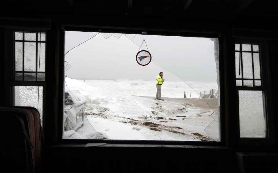A Salisbury, Mass. police officer stands on the beach surveying the damage to a house which was hit by a wave and flooded Saturday, Feb. 9, 2013. A behemoth storm packing hurricane-force wind gusts and blizzard conditions swept through the Northeast overnight. (AP Photo/Winslow Townson)