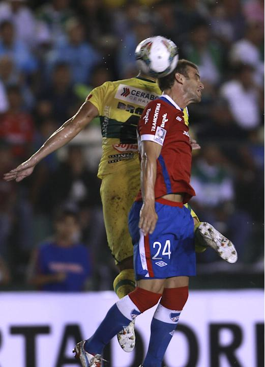 Mariano Brau of Bolivia's Oriente Petrolero, left, fights for the ball with Ivan Alonso of Uruguay's Nacional during a Copa Libertadores soccer match in Santa Cruz, Bolivia, Tuesday, Jan. 28,
