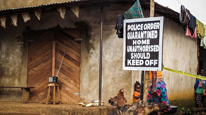 A child, center, stands underneath a signboard reading 'Police order quarantined home unauthorised should keep off' as a family home is placed under quarantine due to the Ebola virus in Port Loko, Sierra Leone, Wednesday, Oct. 22, 2014. U.S. authorities said Wednesday that everyone traveling into the U.S. from Ebola-stricken nations will be monitored for symptoms for 21 days. That includes returning American aid workers, federal health employees and journalists, as well as West African travelers. The program will start Monday in six states that represent 70 percent of people arriving from Liberia, Sierra Leone and New Guinea, said the Centers for Disease Control and Prevention. (AP Photo/ Michael Duff)