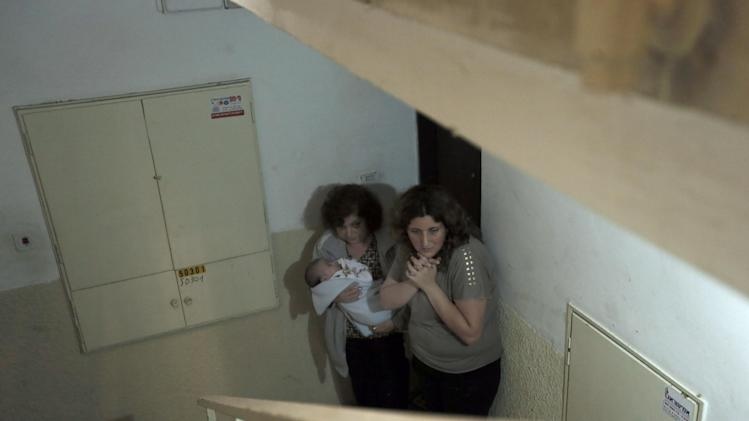 FILE - In this Nov. 19, 2012 file photo, Israeli women take cover in a stairwell as a siren signals the warning of incoming rockets in the coastal city of Ashkelon.  (AP Photo/Tsafrir Abayov, File)