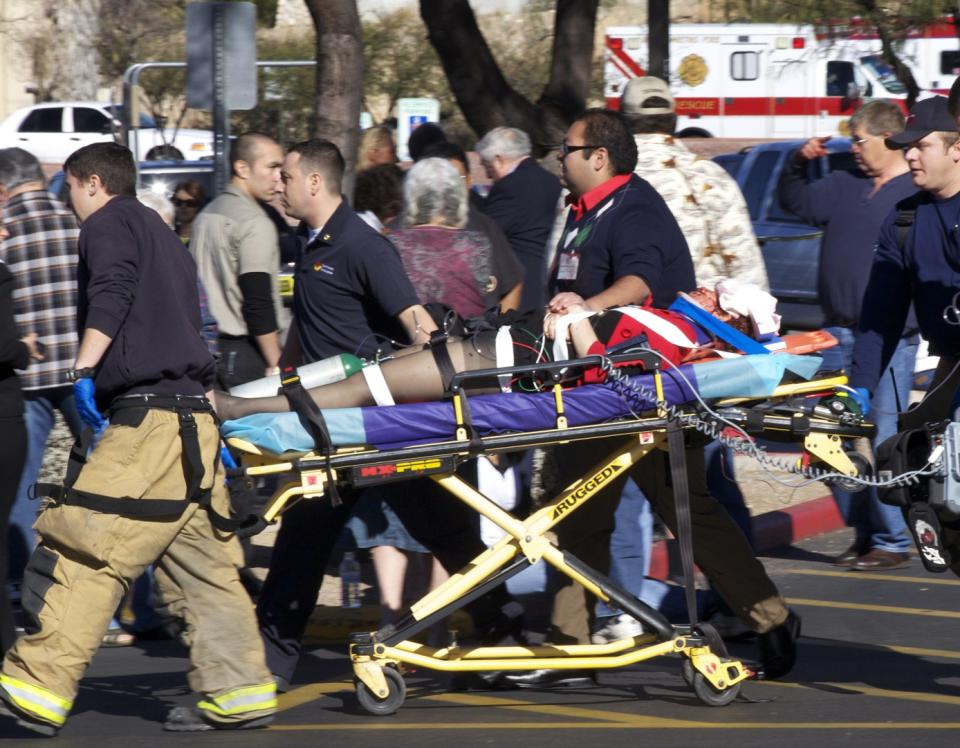 Emergency personnel and Daniel Hernandez, an intern for U.S. Rep. Gabrielle Giffords, second right, move Giffords after she was shot in the head outside a shopping center in Tucson, Ariz. on Saturday, Jan. 8, 2011. (AP Photo/James Palka)