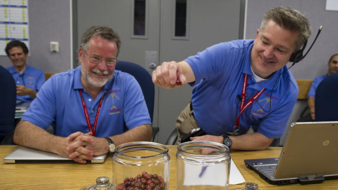 "In this photo provided by NASA, Mars Science Laboratory (MSL) Flight Systems Chief Engineer Rob Manning, left, smiles as he watches MSL Flight Director Keith Comeaux move the final marble from a jar marked ""Days Until Entry"" to the jar marked ""Days Since Launch"" at the Jet Propulsion Laboratory on Sunday, Aug. 5, 2012 in Pasadena, Calif. The MSL Rover named Curiosity was designed to assess whether Mars ever had an environment able to support small life forms called microbes. Curiosity is due to land on Mars at 10:31 p.m. PDT on Aug. 5, 2012. (AP Photo/NASA, Bill Ingalls)"