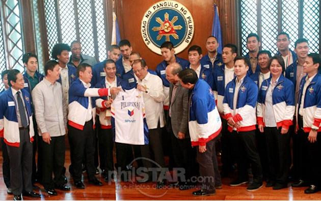 President Aquino receives a Smart Gilas II Pilipinas jersey from head coach Chot Reyes as members and officials of the victorious squad made a courtesy call at Malacañang yesterday following the Natio