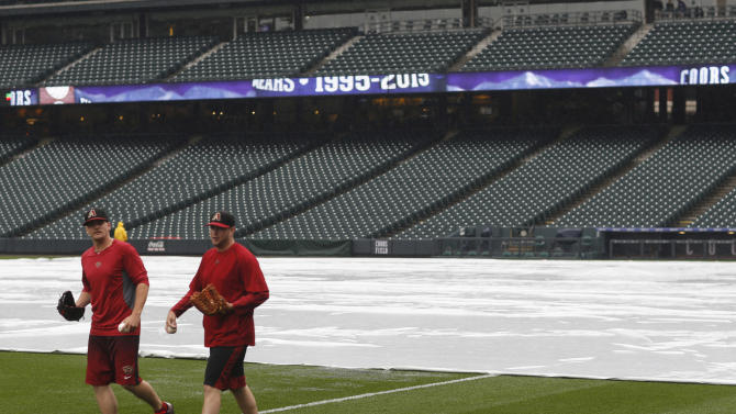Members of the Arizona Diamondbacks walk past the tarpaulin covering the infield after the baseball game against the Colorado Rockies was canceled Tuesday, May 5, 2015, at Coors Field in Denver. The first two games of the three-game series have been canceled by heavy rain that has settled over the intermountain West since late last week. The Diamondbacks and Rockies are scheduled for a doubleheader Wednesday. (AP Photo/David Zalubowski)